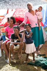 Families share temporary living space beneath a tarp made from a billboard in Petit-Goâve, Haiti. Seated are: Sonia Jean with her daughters Milord Missoule and Fadianie Jean. At rear are Marie Denise Lemaine and her son Samuel. A UMNS photo by Mike DuBose.