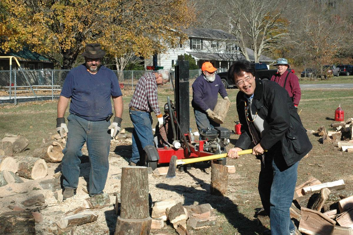 Bishop Jeremiah Park of the Harrisburg Area takes a swipe at chopping firewood as the Rev. David Anderson watches. Anderson (in the brown hat), pastor at First United Methodist Church of Copperhill, Tenn., is a member of a mission team working at Cherokee UMC this week.. A UMNS photo by Annette Spence.