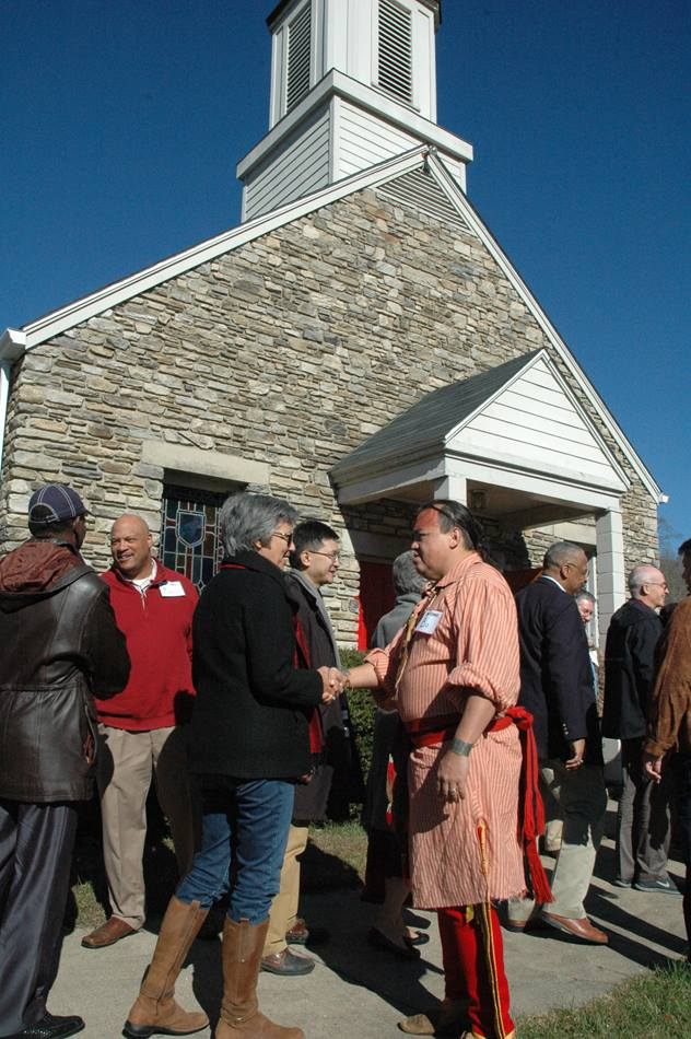Bishop Hope Morgan Ward of the Raleigh Area is greeted by Bo Taylor (dressed in Native American clothing) as bishops arrive at Cherokee United Methodist Church on Nov. 13. A UMNS photo by Annette Spence.