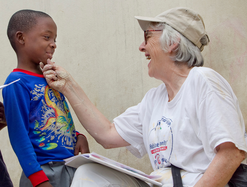 Her hands spattered with paint, United Methodist volunteer Kathy Ahmad takes a break from renovating the Methodist Children's Home orphanage in Port-au-Prince, Haiti, to play a game with Franckenson Renevil. A UMNS photo by Mike DuBose.