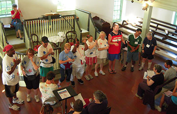 Deaf adults from Camp Pecometh sing during worship at Barratt's Chapel in Frederica, Del. They are encouraged by Bishop Peggy Johnson (rear). A UMNS photo by Barb Duffin.
