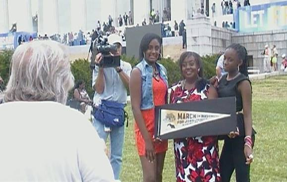 Edith Lee-Payne (holding banner) poses with her granddaughters Destiny (left) and Dejai during the 50th anniversary of the March on Washington. Making their family portrait is Rowland Scherman, who made an iconic photograph of Edith during the 1963 march.