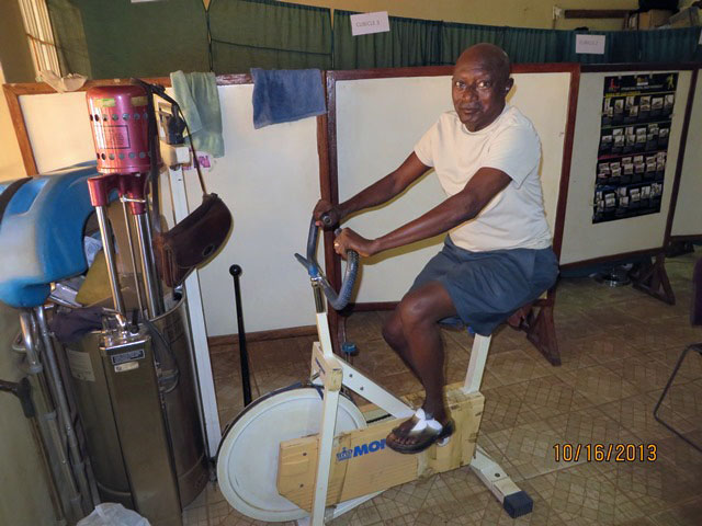The Rev. Steven Momoh Momo-Jah, a United Methodist pastor, works on physical exercise at the physical therapy unit. Photo by Phileas Jusu, UMNS.