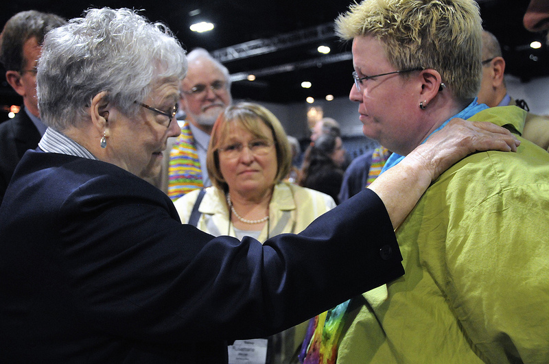 Bishops Judith Craig (left), Scott Jones (behind Craig) and Rosemarie Wenner (center) negotiate with the Rev. Amy DeLong, after dozens of demonstrators demanding a more inclusive church took over the floor of a May 3 session of the 2012 United Methodist General Conference in Tampa, Fla. The three bishops talked with DeLong in an attempt to resolve the situation without resorting to arrests.