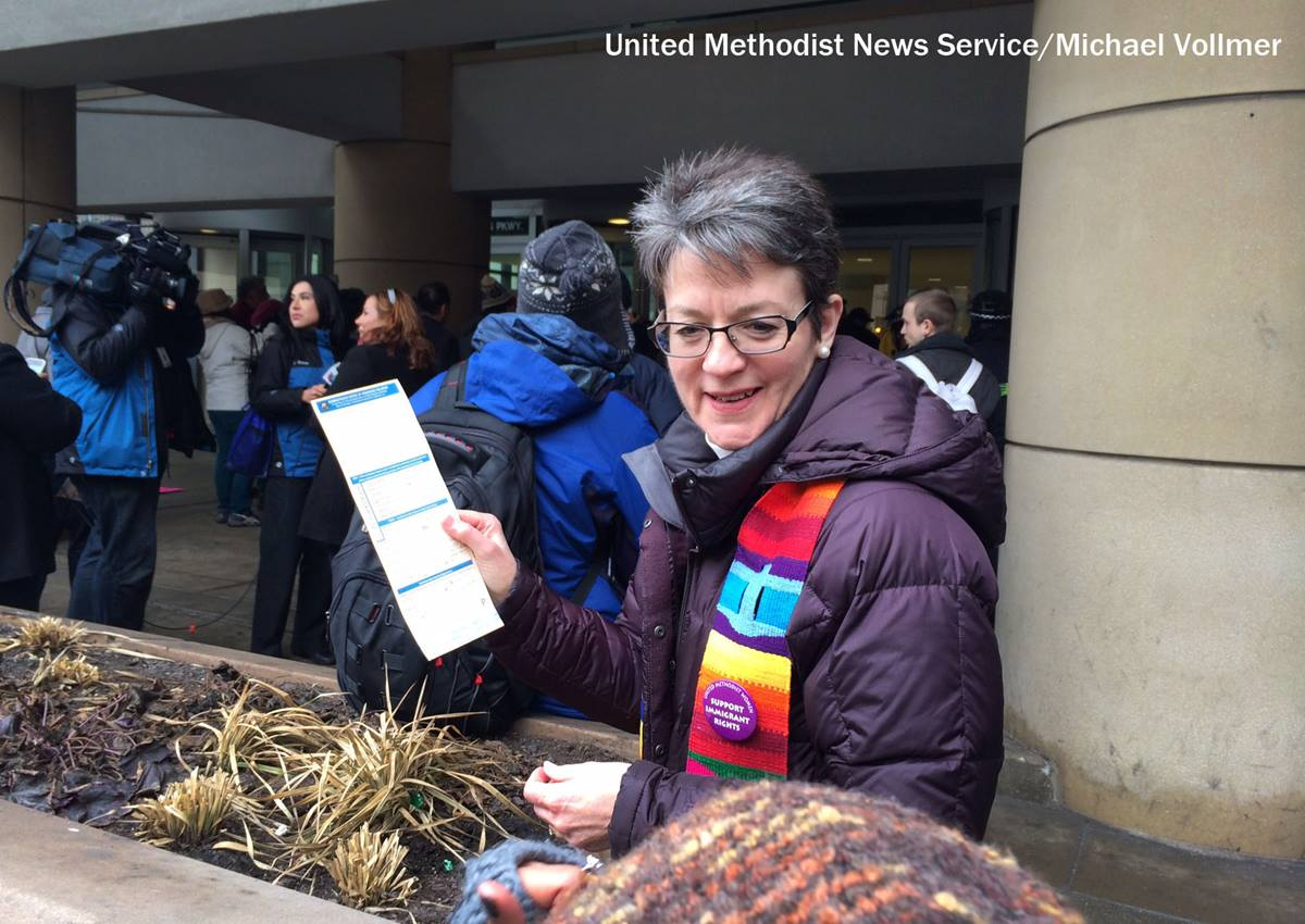 United Methodist Bishop Sally Dyck, Chicago holds a citation for criminal trepassing outside the ICE office. The citation followed the rally and protest calling upon President Obama to stop deportations of undocumented people. Photo by Michael Vollmer, UMNS.
