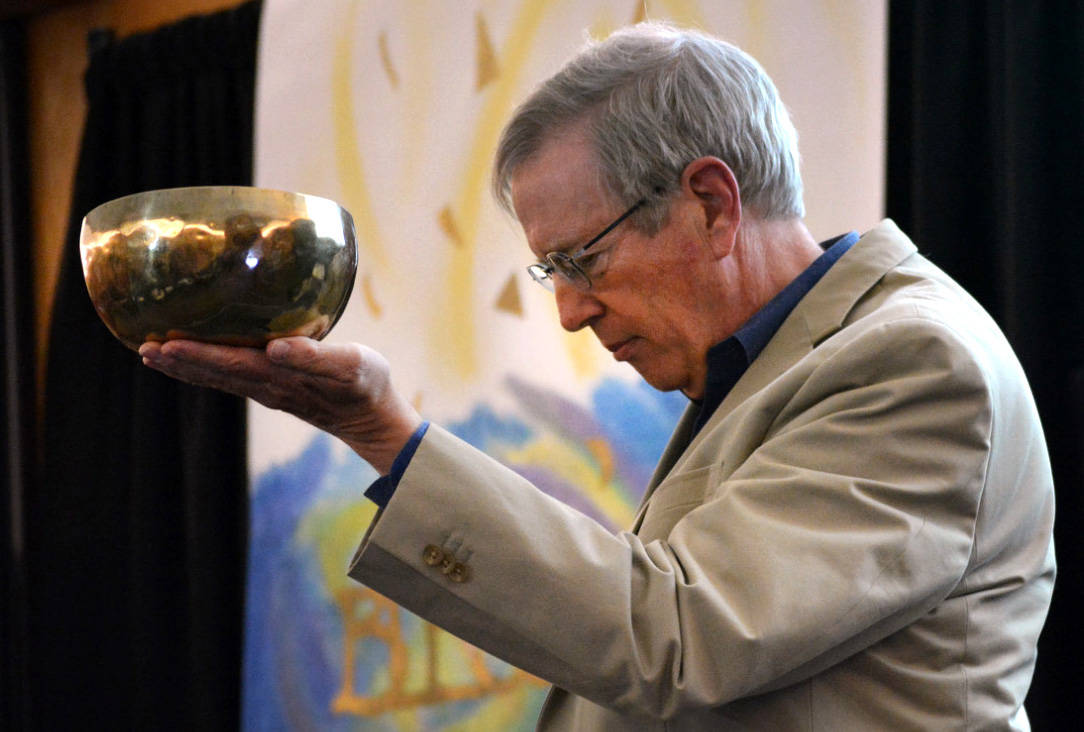 """Bill Everett holds a Tibetan Buddhist singing bowl to """"summon the gathering to peace"""" during the opening of the Peace Conference.  Photo by Michael Rich."""