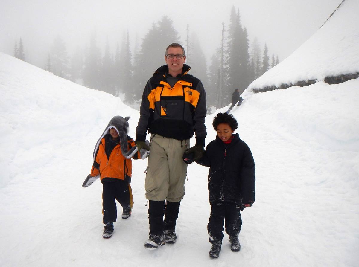 Scoutmaster Geoffrey McGrath walks with Davonn Abaga and Denzel Abaga, two members of the Cub Scout pack, during an outing to Mount Rainier National Park. Photo by Nguyen Truong, Cubmaster.