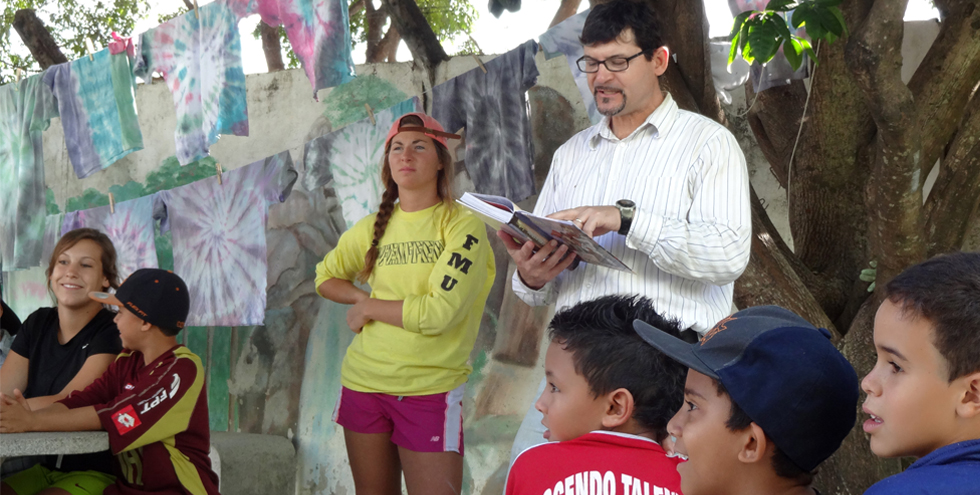 Phil Wingeier-Rayo, professor of religion at Pfeiffer University, reads the Bible to children in a vacation Bible school class during a Pfeiffer University mission trip to Brazil in June 2013. Photo by Diana Wingeier-Rayo.