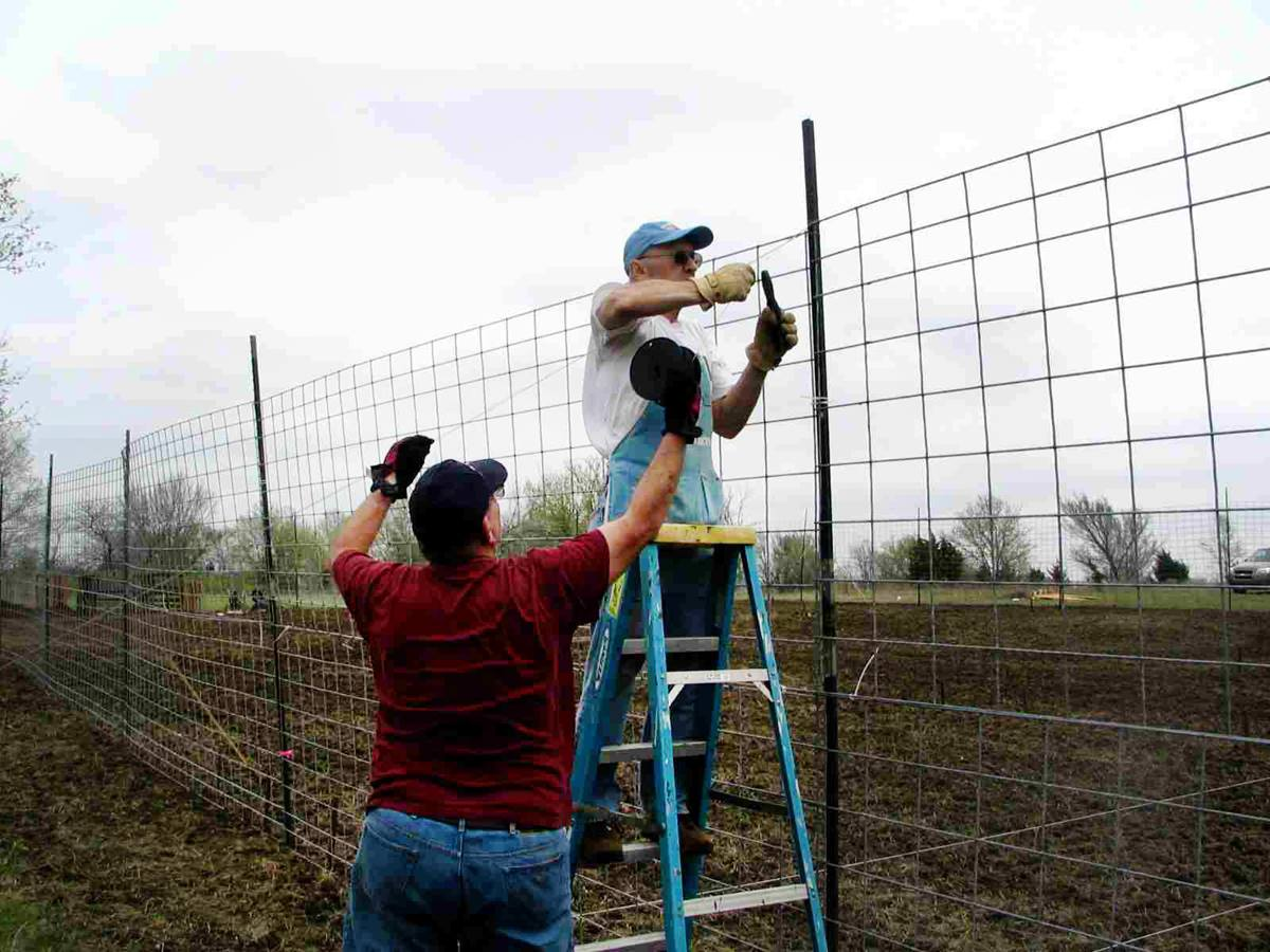 """Volunteers with Bartlesville First Church prepare the fencing for their community garden in order to """"keep the critters out."""" The project started as a 2009 Change the World project."""
