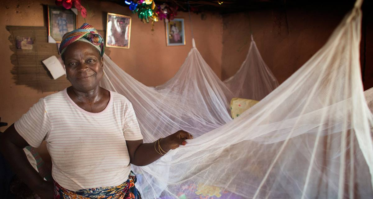 Matilda Ndanema displays the insecticide-treated mosquito net she received in 2010 from the United Methodist Church's Imagine No Malaria campaign at her home in Bumpe, Sierra Leone.