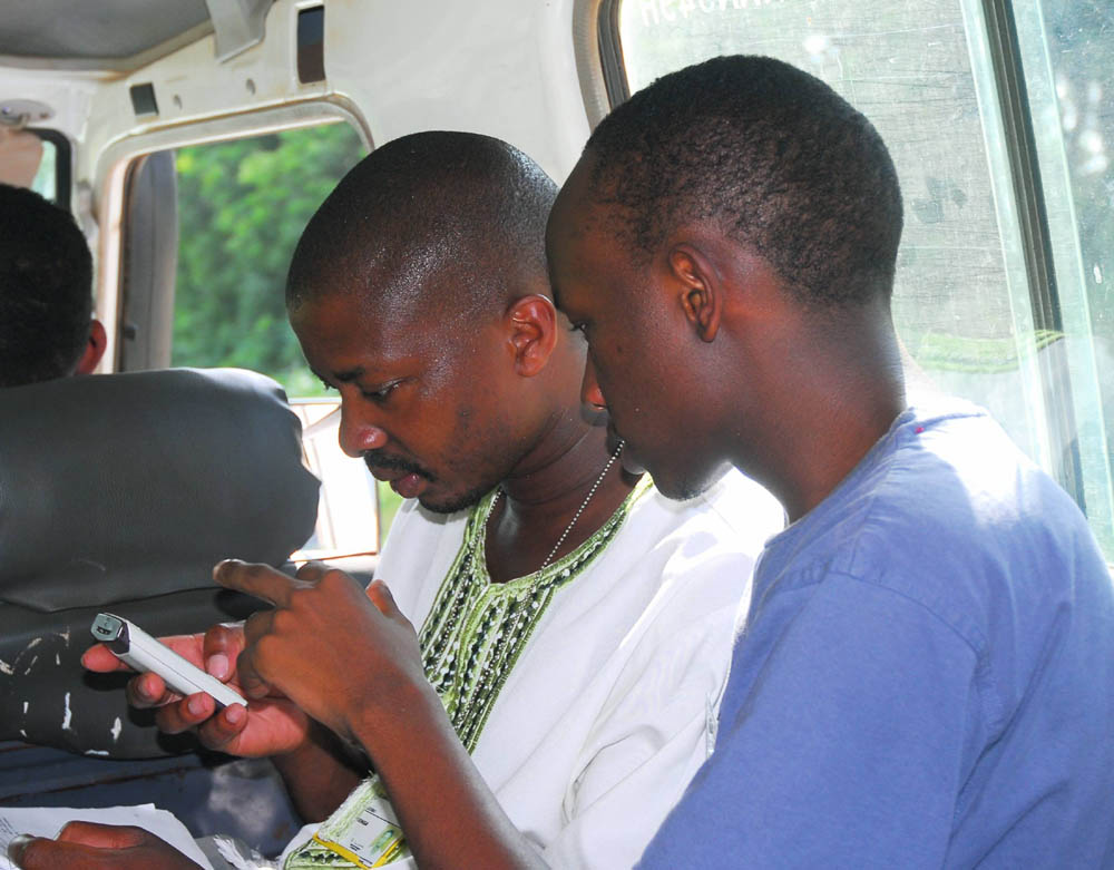 Two Kenyan men send text messages. Photo courtesy of Ken Banks, kiwanja.net.