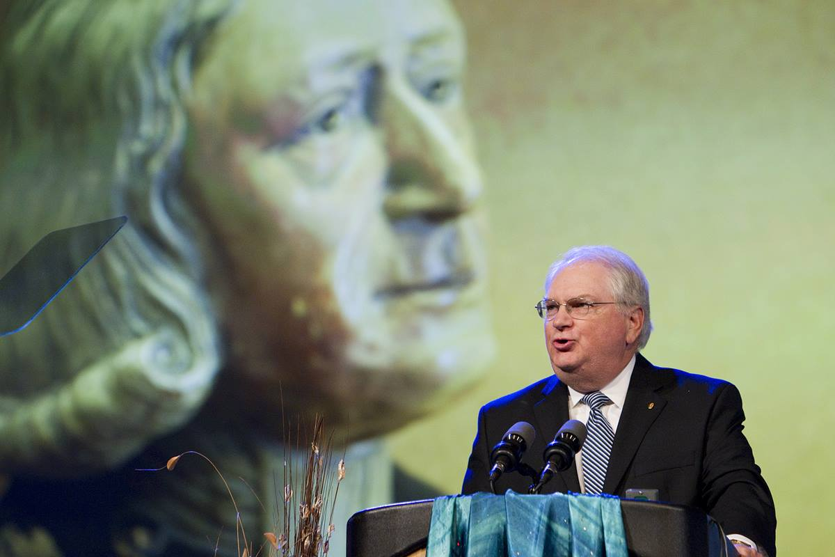 The Rev. Robert J. Williams, backed by a video image of John Wesley, discusses the work of the United Methodist Commission on Archives and History during the denomination's 2012 General Conference in Tampa, Fla. Williams retires Aug 1, 2014. Photo by Mike DuBose, UMNS.