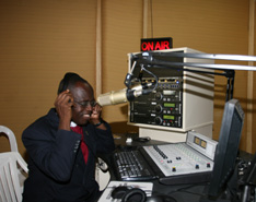 Bishop Boni tries out the equipment at the new station, 'The Voice of Hope.'