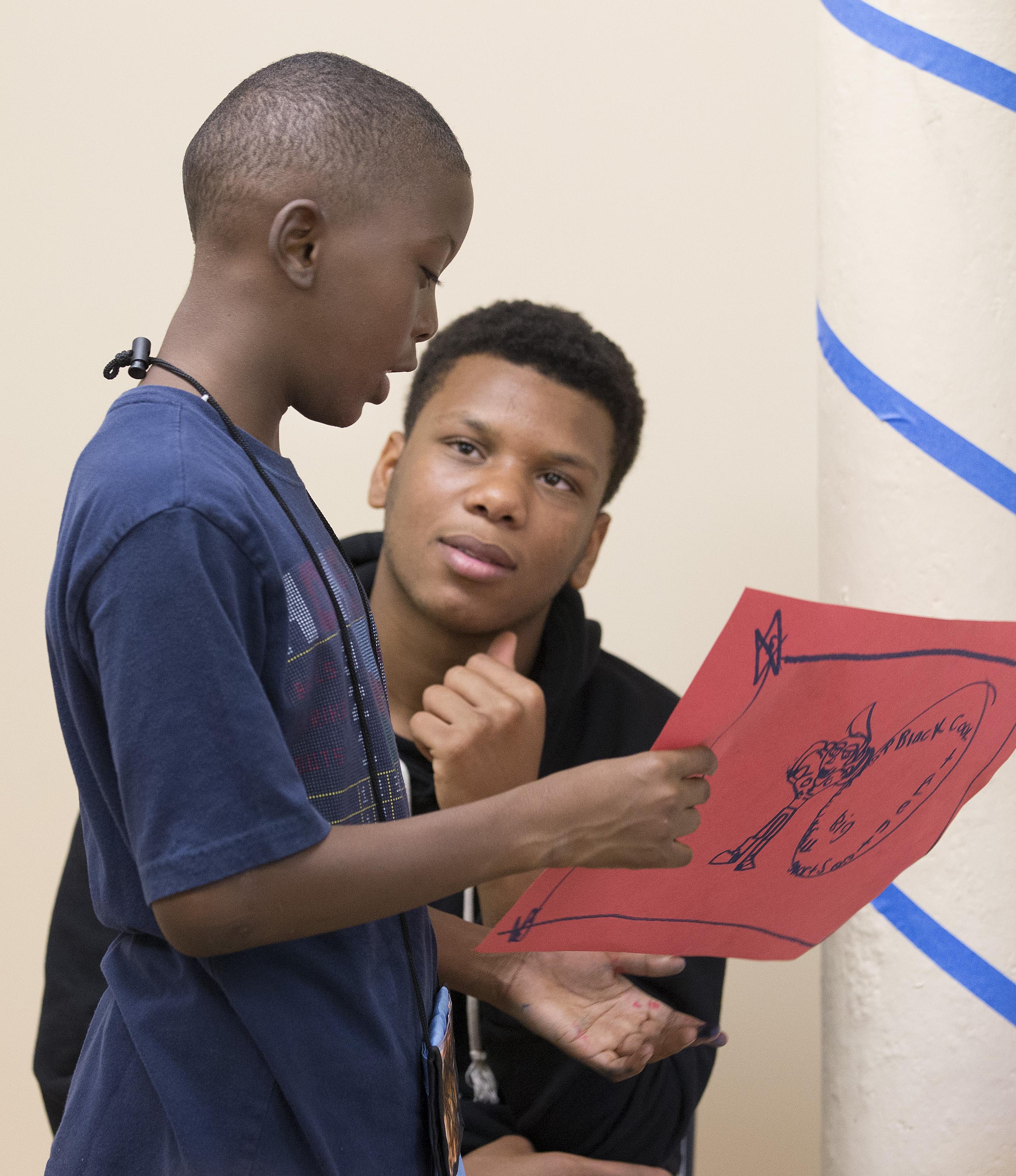 Teen volunteer Tra'Sean, right, encourages 6th-grader J.B. to explain his drawing at the Freedom School at Gordon Memorial United Methodist Church in Nashville, Tenn.