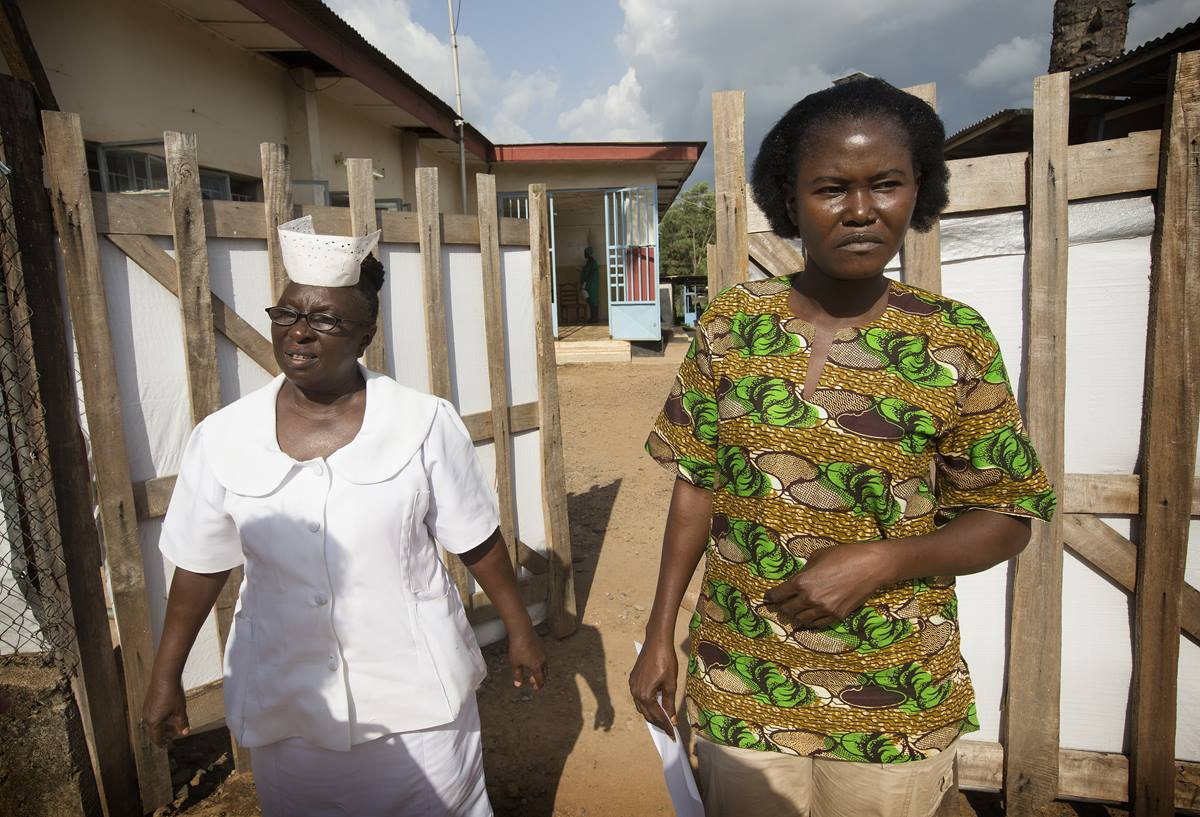 Mbalu Fonnie, head nurse in the hemorrhagic fever ward, and nurse Veronica Karoma describe efforts to contain the Ebola virus as she stands outside the gates to the isolation ward at the government hospital in Kenema, Sierra Leone.