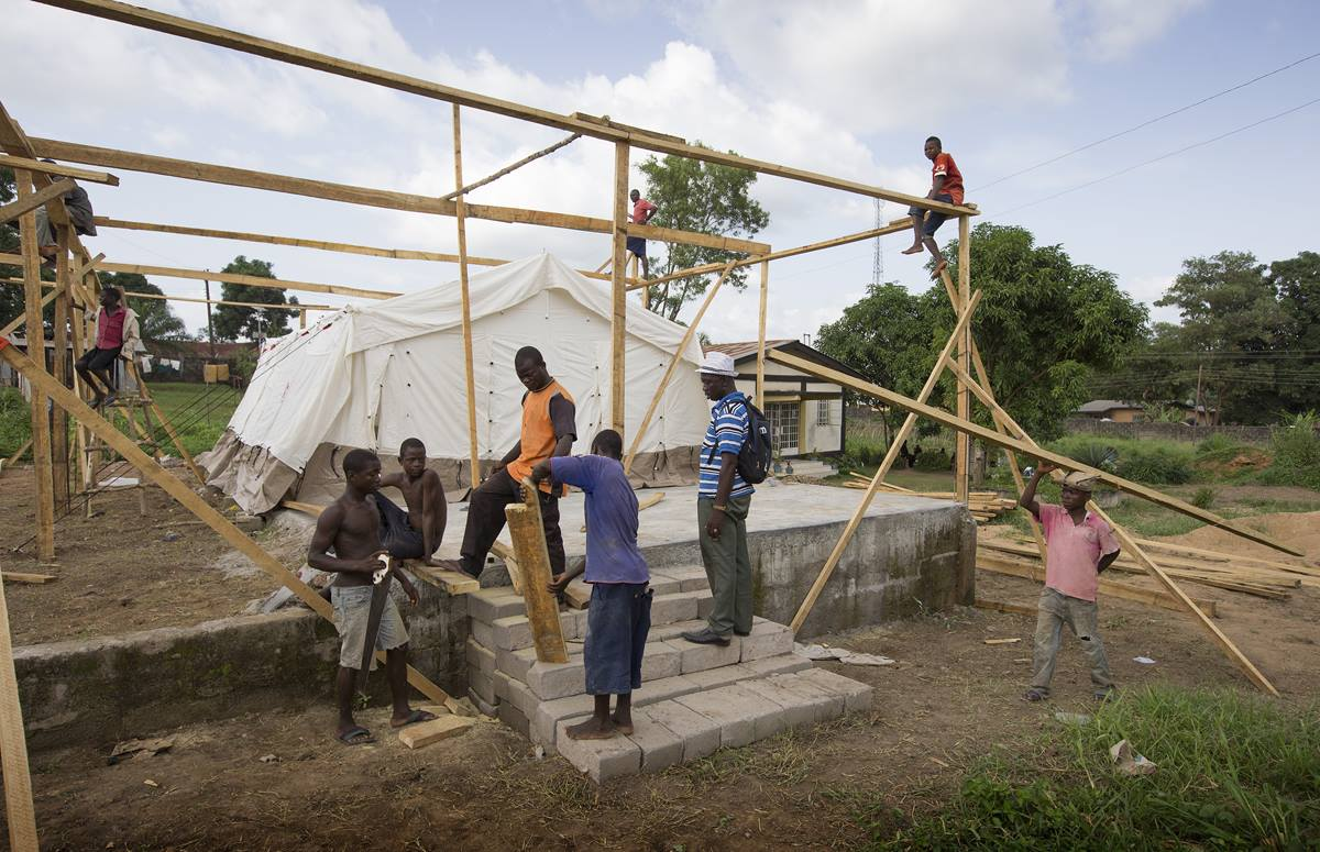 Workers erect a temporary isolation ward for patients with the Ebola virus at the government hospital in Kenema, Sierra Leone.