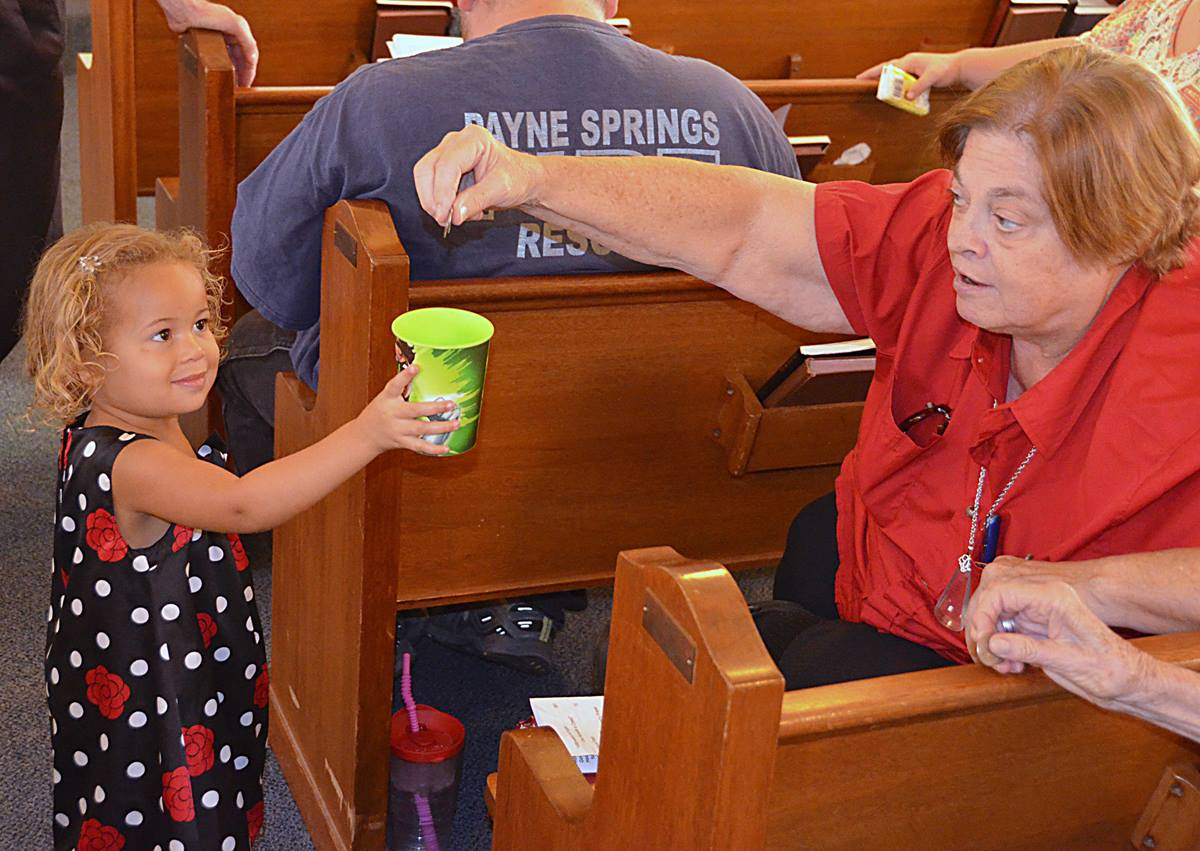 Alaia Williams collects a quarter from member Dennise Richardson at Aley United Methodist Church in Seven Points, Texas. Photo by Richard Browne.
