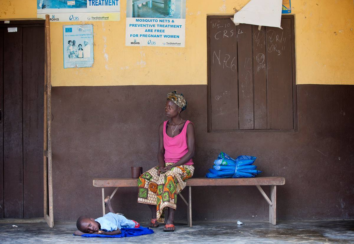 Digba Massaquoi waits with her 5-year-old son, Lahai, who is ill, at the health clinic in Benduma, outside Bo, Sierra Leone. Beside her on the bench are insecticide-treated mosquito nets provided by the United Methodist Church's Imagine No Malaria initiative as part of an integrated health campaign during Sierra Leone's national Maternal and Child Health Week. Photo by Mike DuBose, UMNS.