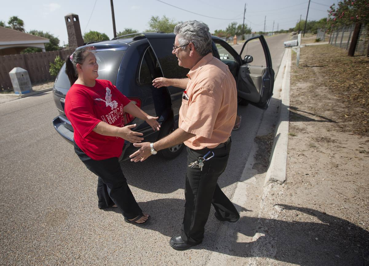 Sanuanita Leal (left) greets the Rev. Javier Leyva near her home in Mission, Texas. Leyva, now director of immigration ministries for The United Methodist Church in South Texas, previously served as her pastor and baptized Leal and her family.