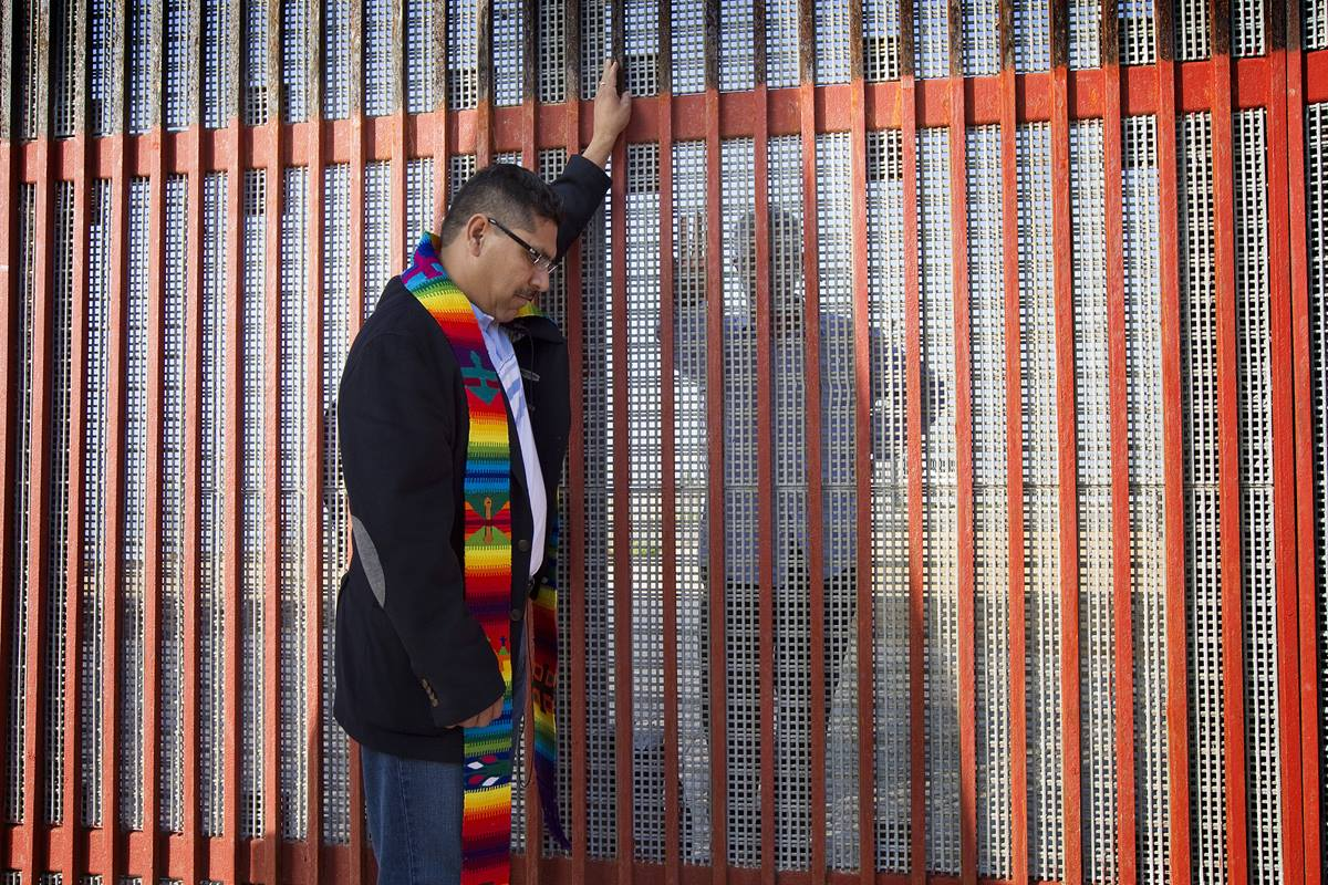 The Rev. Saul Montiel (right) prays during a cross-border service of Holy Communion at El Faro park in Tijuana, Mexico. Montiel is on the Mexico side of the border.