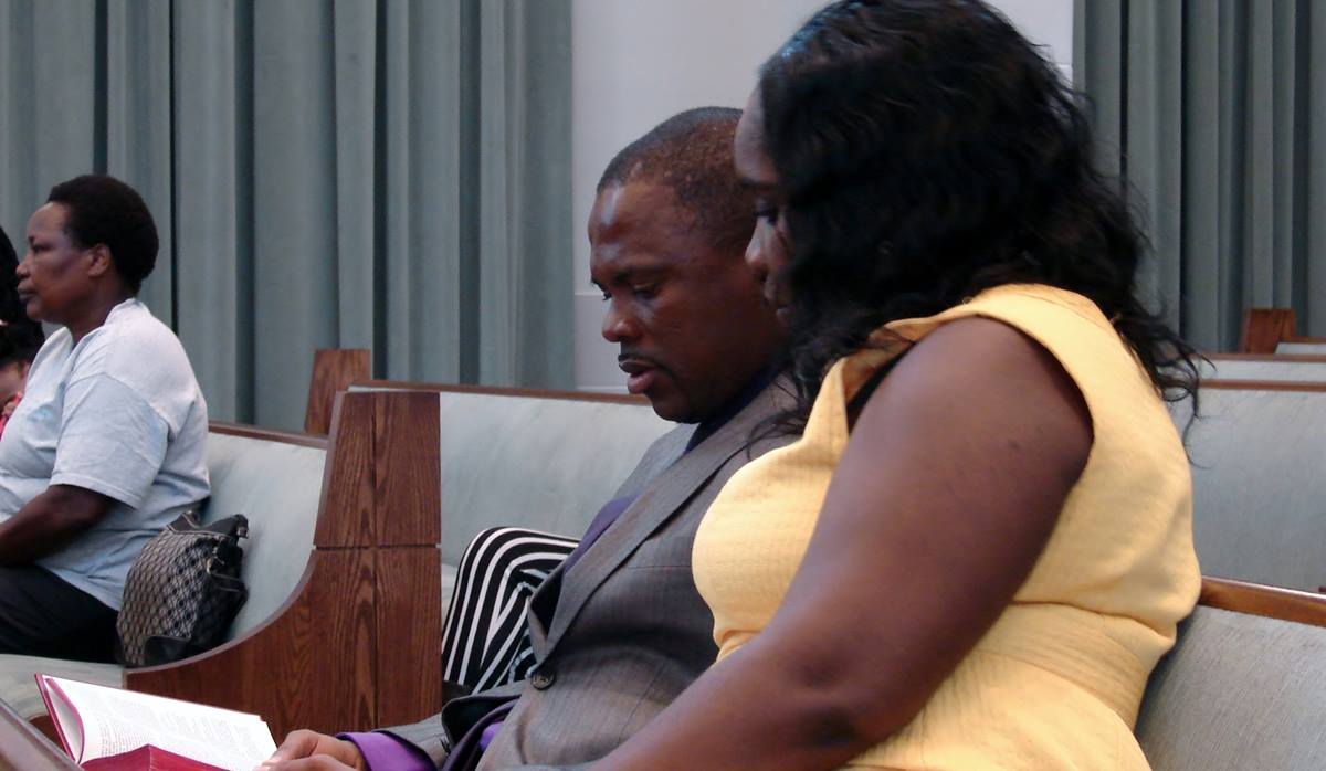 Melvin Morgan and his wife, Juriciah, follow the Scripture reading during the service. Morgan has lost a sister and two nieces to the Ebola epidemic in his home country, Liberia.