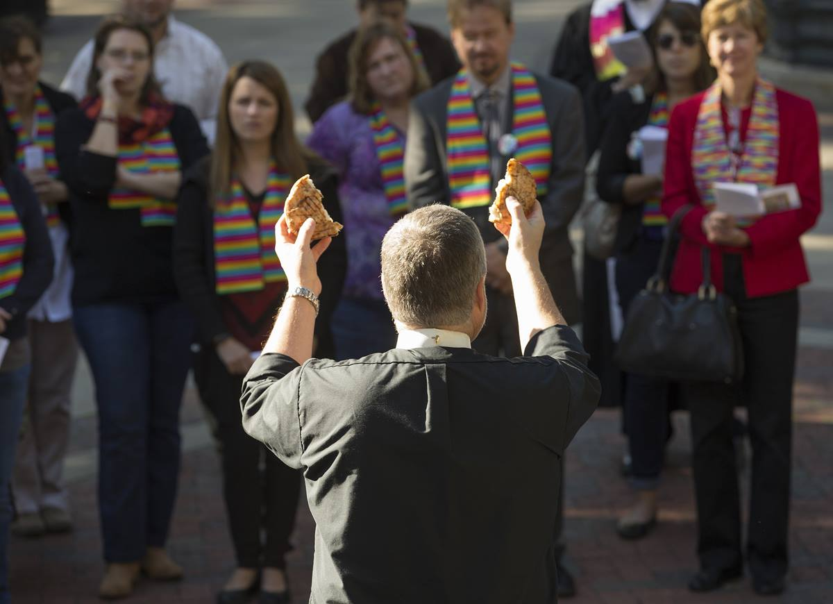 The Rev. Johnny Jeffords blesses the elements of Holy Communion during a prayer service for unity at Court Square Park in Memphis, Tenn., prior to the Rev. Frank Schaefer's appearance before the United Methodist Judicial Council. Schaefer is directly behind Jeffords' right hand.