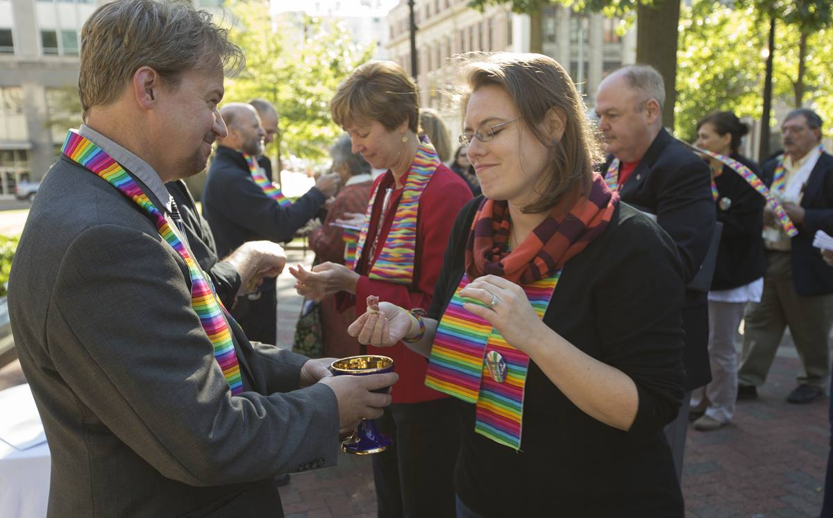 The Rev. Frank Schaefer (left) serves Holy Communion during a prayer service for unity at Court Square Park in Memphis, Tenn., prior to his appearance before the United Methodist Judicial Council.