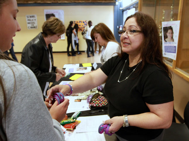 Ann Brownell gives out Amanda Network wrist bands at Andrew Hill High School.