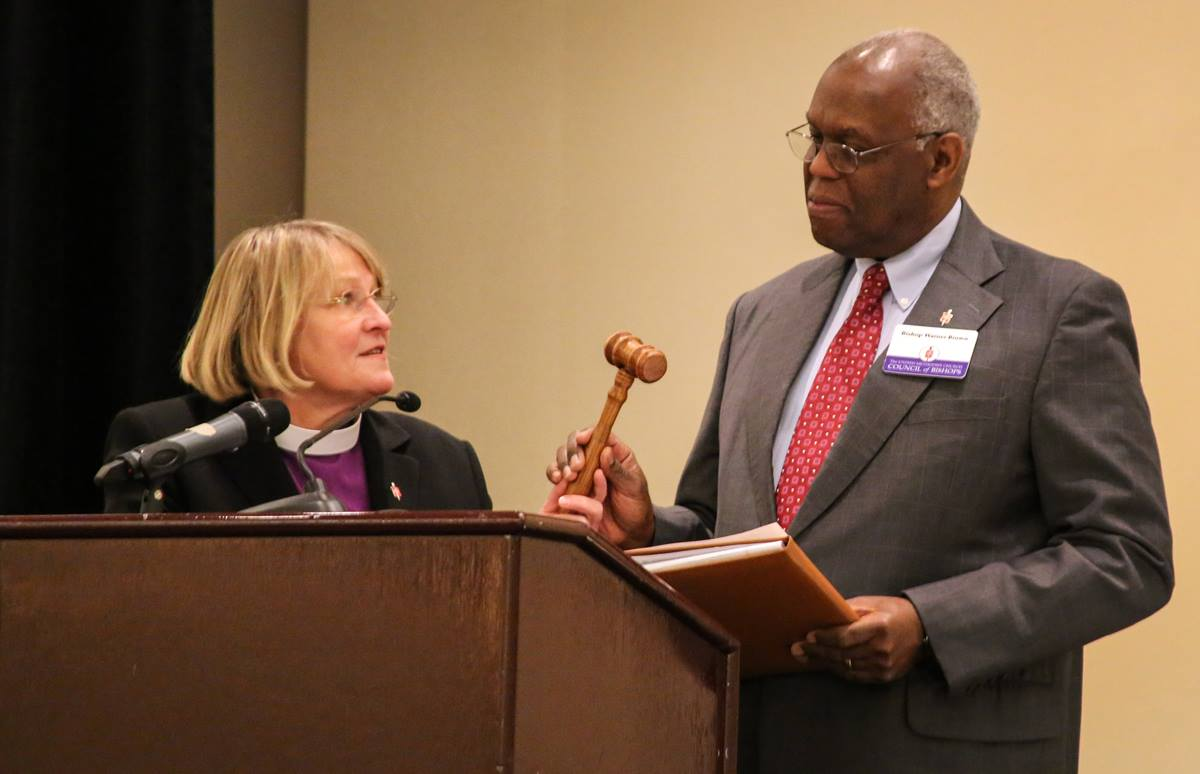 Bishop Warner H. Brown Jr., the new president of the Council of Bishops, accepts the gavel from Bishop Rosemarie Wenner in a ceremony Nov. 3 in Oklahoma City. Photo by Andrew Jensen, United Methodist Communications