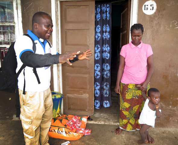 The Rev Sylvester Holima prays with Hawa Bockarie, bereaved wife of the Rev. Samuel Bockarie, who died of Ebola. He prays for God's strength and provision for the family.