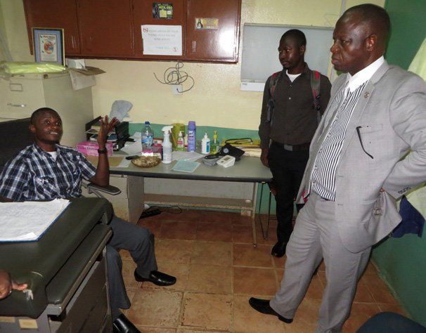 Bishop John K. Yambasu (standing, right) and senior conference staff visit and pray with Dr. Martin Salia (sitting) after a patient admitted to Kissy General Hospital died of Ebola.