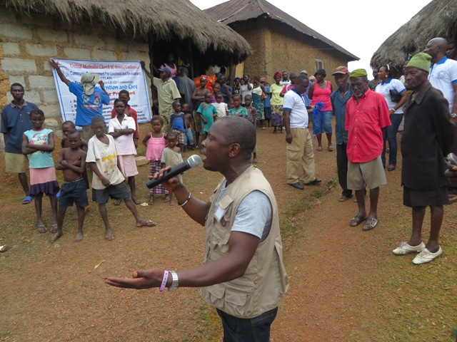 The Rev. Michael Gbenday gives an educational program about Ebola in Mende, the local language of the people of Moyollo village in Sierra Leone. Photo by Phileas Jusu, UMNS