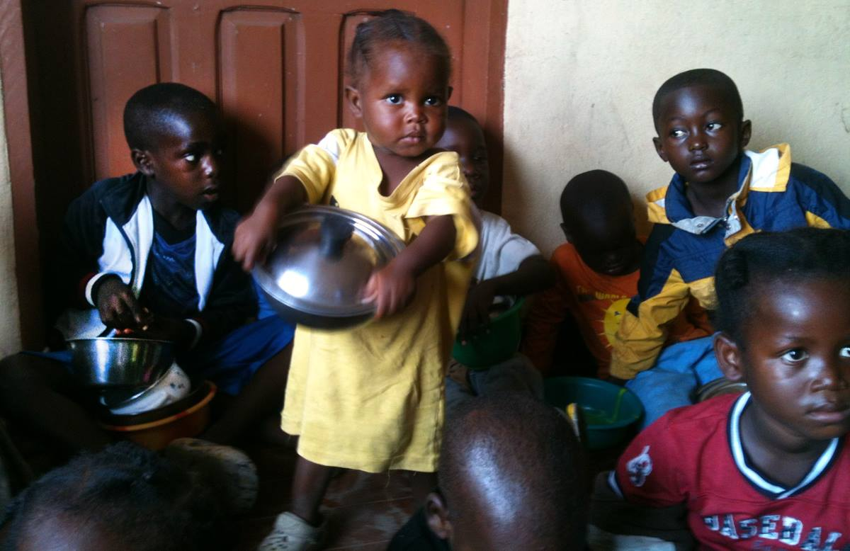 Children hold bowls of food served by a feeding initiative created by a United Methodist pastor to feed Ebola orphans and those quarantined during the Ebola crisis. Hundreds of children are fed in the slum community of West Point in Monrovia.