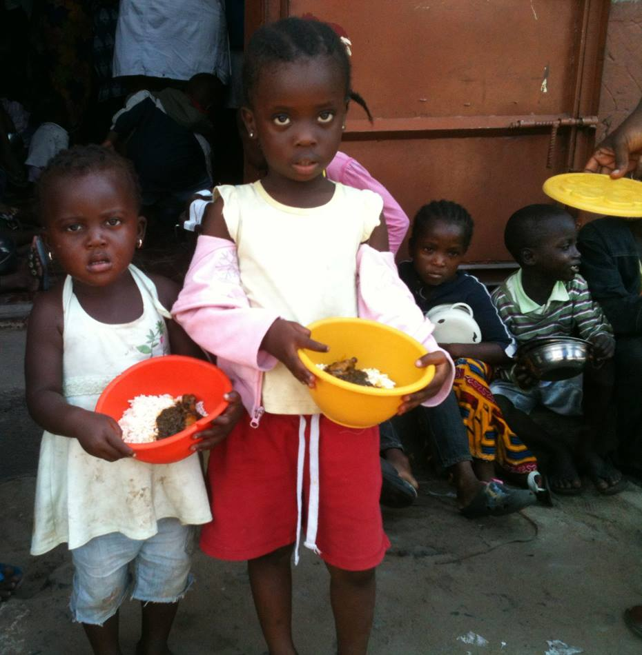 Two young girls receive meals from a program started by a United Methodist pastor for children living in West Point, a slum in Monrovia.