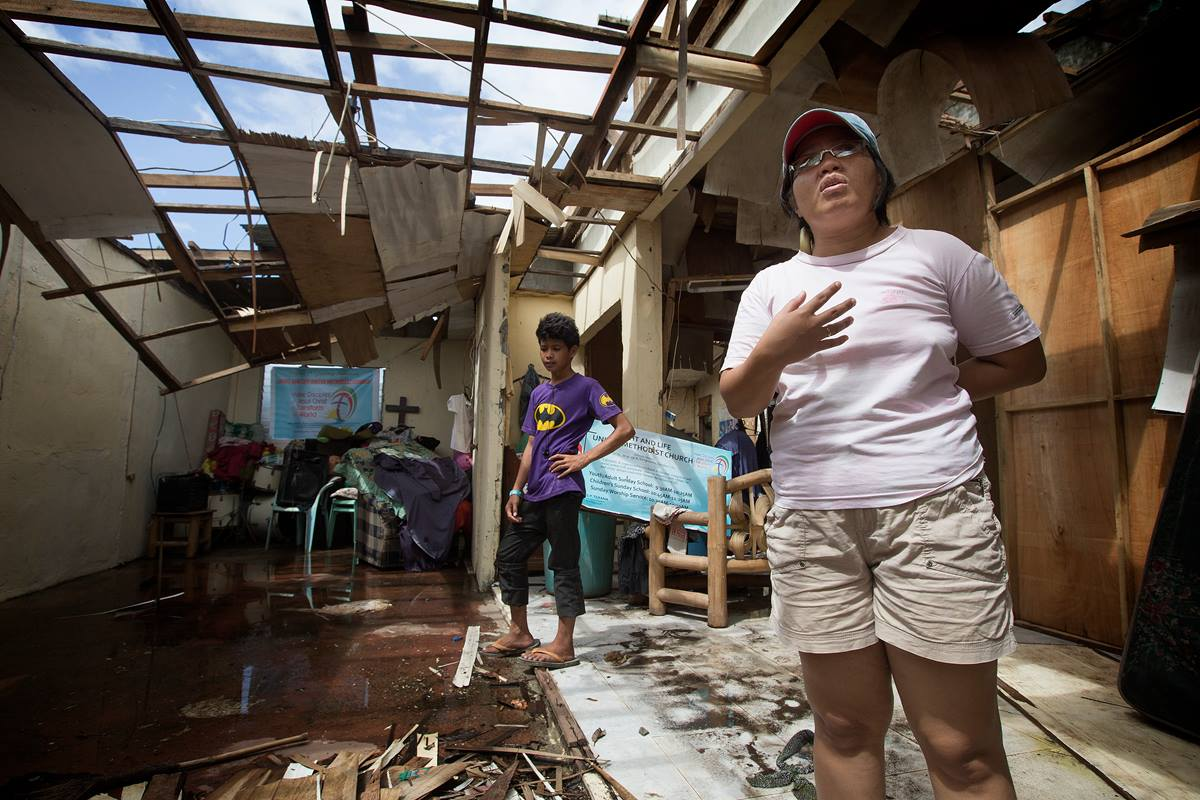 The Rev. Iris Picardal Terana describes how Typhoon Yolanda, also known as Typhoon Haiyan, destroyed Light and Life United Methodist Church in Tacloban City, Philippines in November 2013. The church is using a temporary building one year after the storm. At left is church member Ronell de Juan. File photo by Mike DuBose, UMNS.