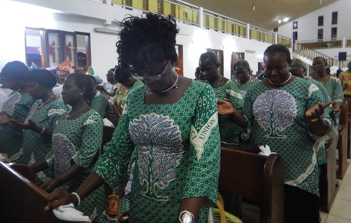 Côte d'Ivoire United Methodist Women bow their heads in prayer at a service celebration the women's partnership with the social media network Pubcell CI. Photo by Isaac Broune, UMNS