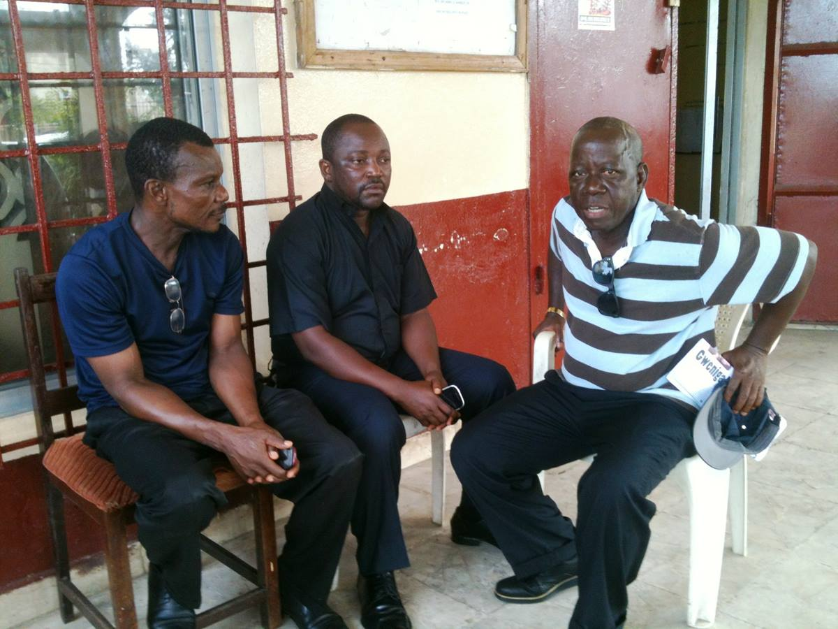 The Rev. P. Harvey Willie, superintendent of the Gbarnga district, talks with two United Methodist clergymen about the Ebola outbreak in Liberia. Willie, center, is shown with the Rev. Boye Davis, left, an instructor at the Gbarnga School of Theology, and the Rev. David Bondo, Jorkoleh district superintendent. UMNS photo by Julu Swen