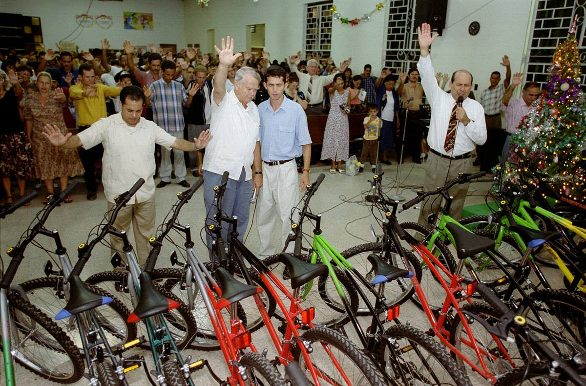 The Rev. H. Eddie Fox (second from left) and Bishop Ricardo Pereira Diaz of the Methodist Church in Cuba (right) bless bicycles donated by World Methodist Evangelism to Cuban lay pastors during a service at J.W. Branscomb Methodist Church in Holguin, Cuba in 2002.
