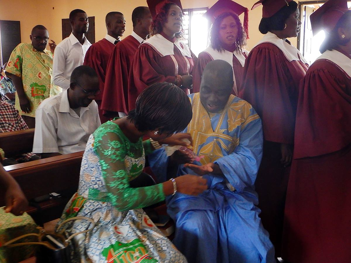 United Methodist preacher, Victor Gnangbi, and Claudia N'Guessan use hand sanitizer before communion at a United Methodist church in western Côte d'Ivoire. Photo by Isaac Broune, UMNS