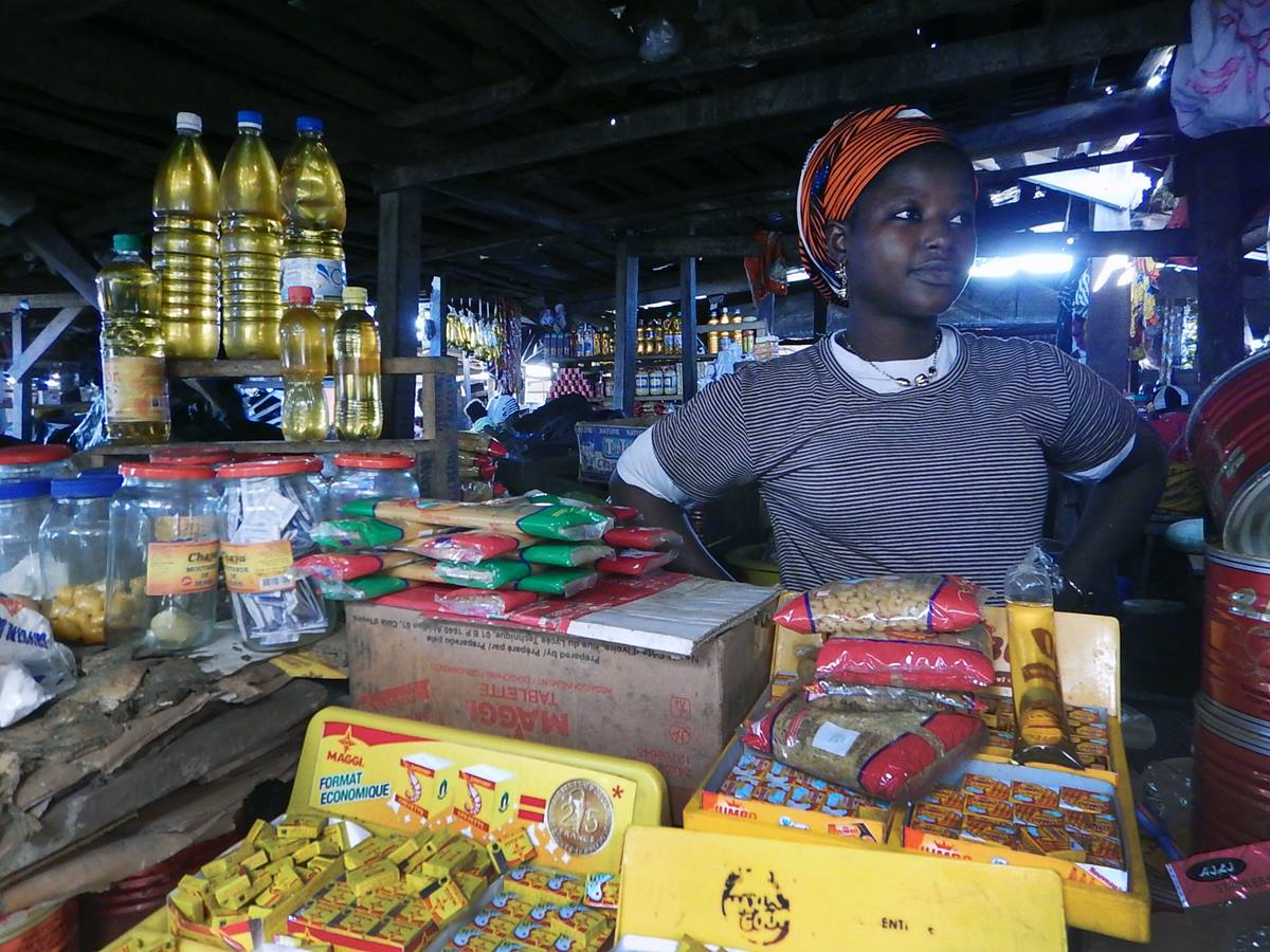 Fanta Touré stands in her stall in the market in Man, Côte d'Ivoire.  Her items for sale range from packaged food to oil and are imported from neighboring Guinea. Photo by Isaac Broune, UMNS