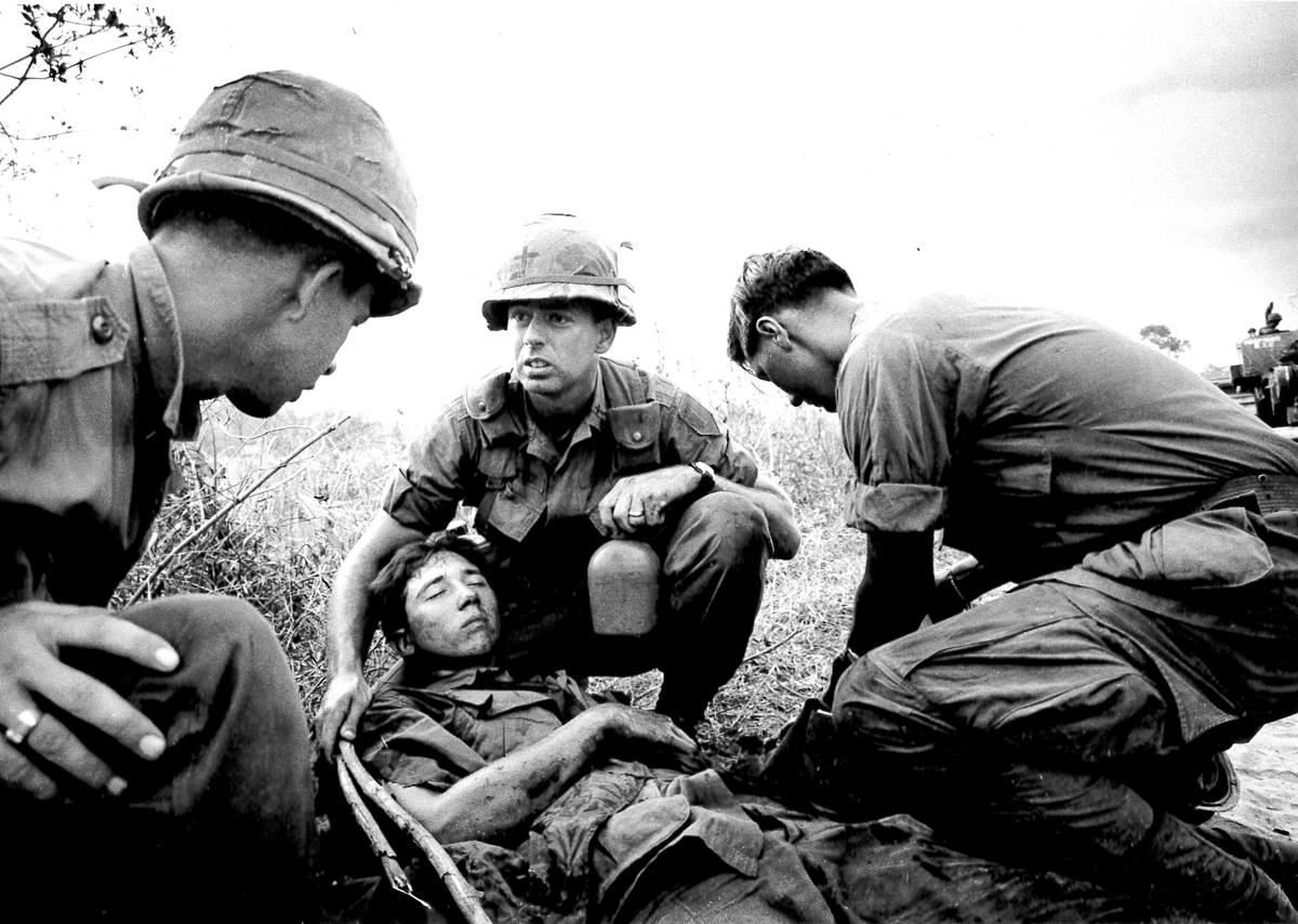 "United Methodist Chaplain William ""Tom"" Carter (center), age 26, helps an injured man whose truck hit a mine 30 miles north of Saigon, Vietnam. Carter added the cross to his helmet with a grease pencil."