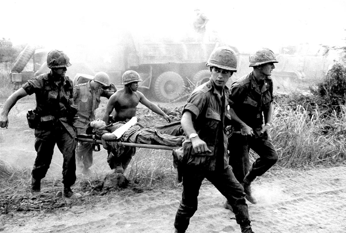 Chaplain Carter (far left) helps bear the wounded man to a medic station before his evacuation to a hospital.