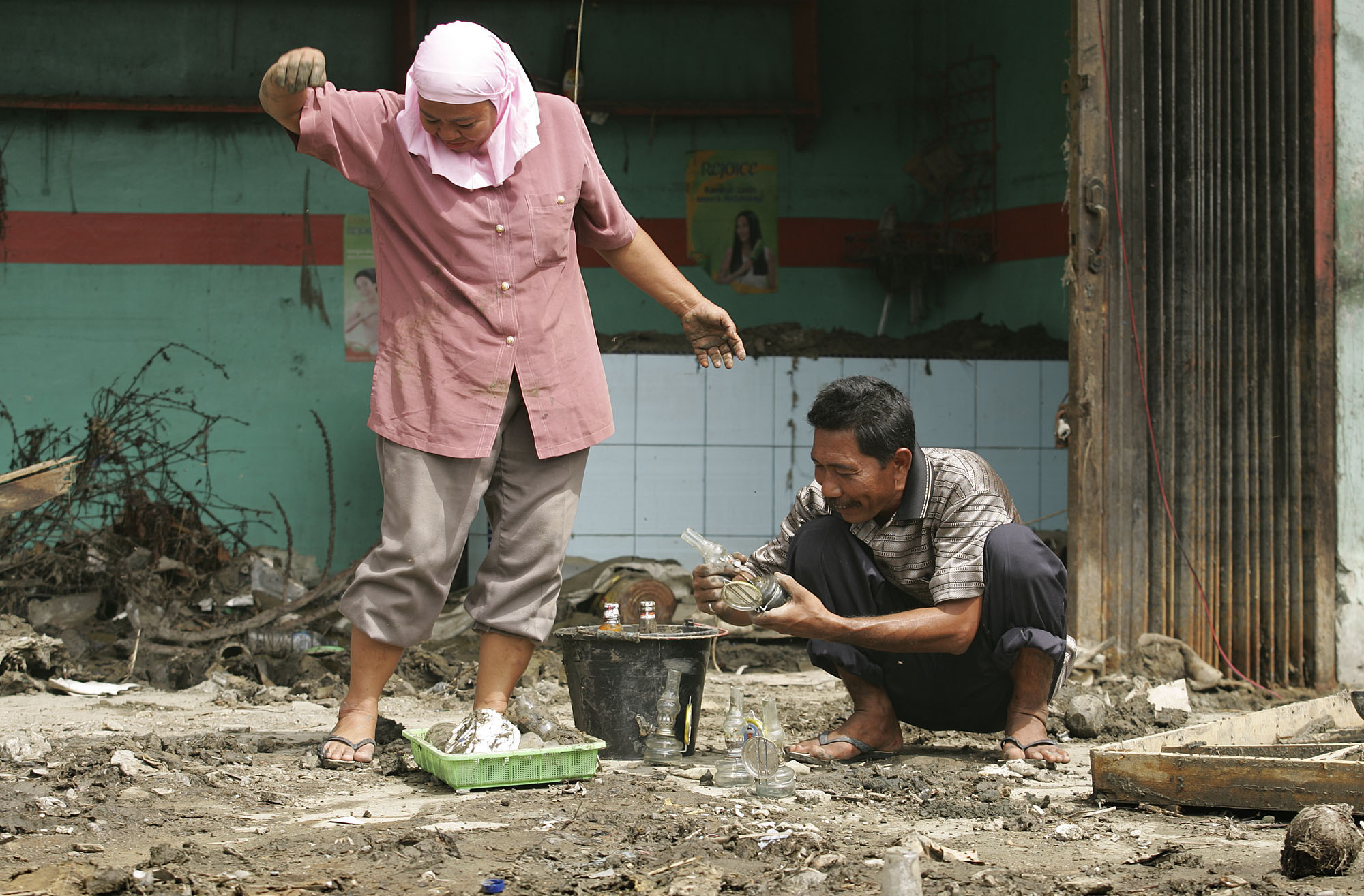 Shopkeepers salvage oil lamps from the wreckage of their store. Photo by Mike DuBose, UMNS.
