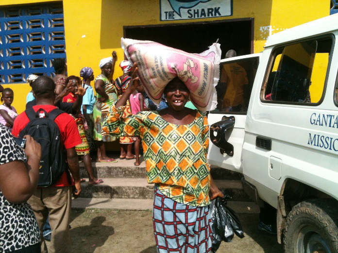 A woman carries a 25-kilogram (55-pound) bag of rice she received through the food distribution in Topoe Village outside Monrovia by the United Methodist Committee on Relief and The United Methodist Church in Liberia. Photo by Julu Swen, UMNS