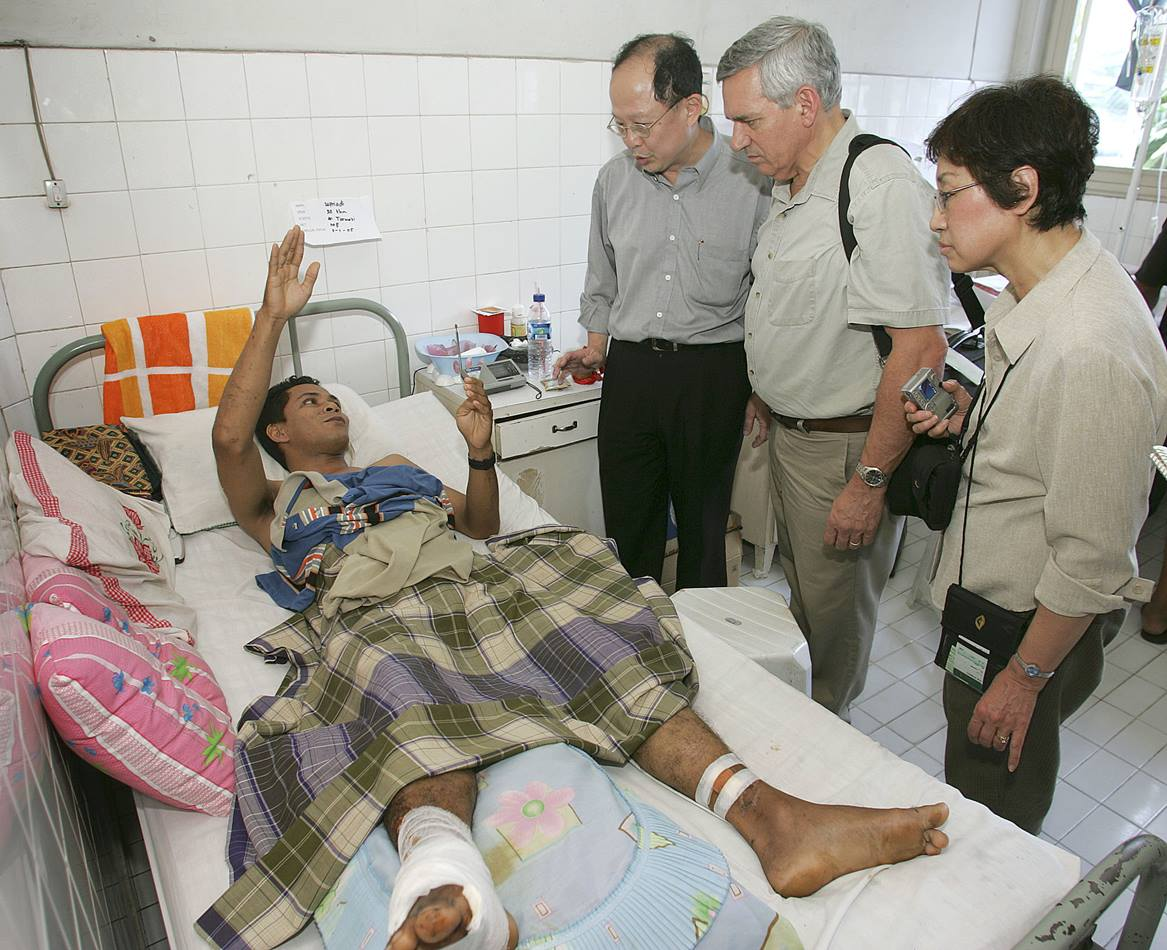 A patient at the Rumah Sakit Methodist Hospital in Medan, Indonesia, describes how he survived the Dec. 26 tsunami that destroyed his home in Banda Aceh. In January, a delegation of mission and communications leaders from the United Methodist church visited areas of Sumatra, Indonesia, near the epicenter of the earthquake that caused the tsunami. From left, center, are Dr. Yohan Pranata, a director of the hospital; the Rev. R. Randy Day, top staff executive of the denomination's Board of Global Ministries; and Kyung Za Yim, president of the Women's Division. Photo by Mike DuBose, United Methodist News Service
