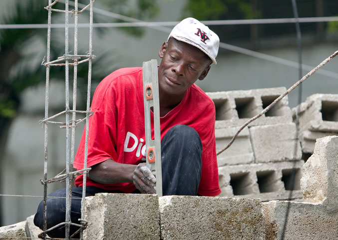 Pierre Michel repairs a wall outside the Methodist Guest House in Port-au-Prince.
