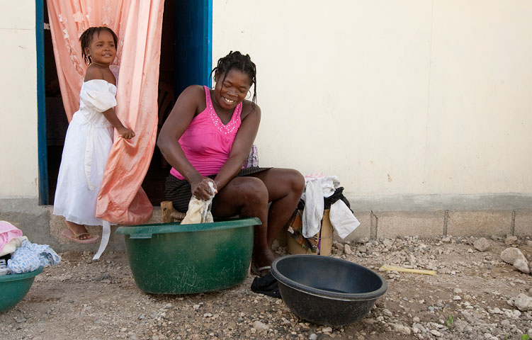 Princifanie washes her family's clothes while her daughter, Deshca, watches in front of their temporary home at Camp Corail.
