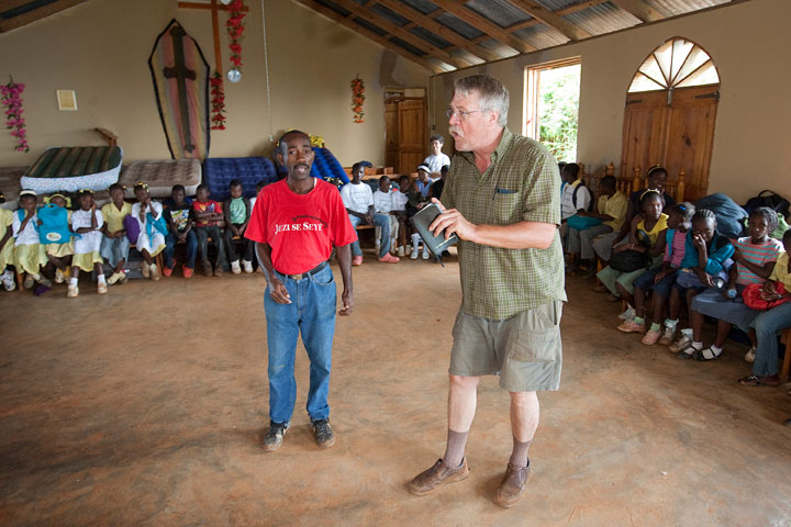 The Rev. Steve Knutsen (right), of Pleasant Valley (N.Y.) United Methodist Church, and translator Jean Claude Degazon tell a story during a vacation Bible school for children at the Methodist church in Furcy, Haiti.