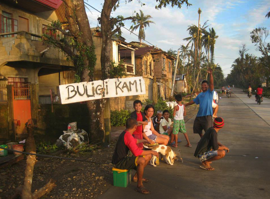 """After Typhoon Hagupit, a family in Taft in the province of Eastern Samar sits by a sign that says buligi kami, which translates """"Help us please."""" Photo by Marlon Paano Lasaca"""