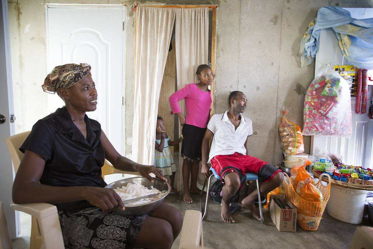 Elisma Cléance (left) and her husband Adma Alicié (right) sell food items and other household goods from the new home they share with their family near Cabaret, Haiti. They are beneficiaries of a neighborhood-based resettlement program implemented by the United Methodist Committee on Relief and the United States Agency for International Development. Photo by Mike DuBose, UMNS